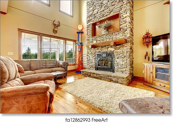 Free art print of Living room with high ceiling, stone fireplace and  leather sofa.