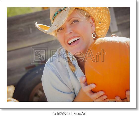 bb01130ffa3 Beautiful Blond Female Rancher Wearing Cowboy Hat Holds a Pumpkin in a  Rustic Country Setting.