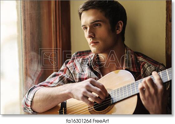 Free art print of He loves the guitar sounds  Handsome young man sitting on  the windowsill and playing guitar