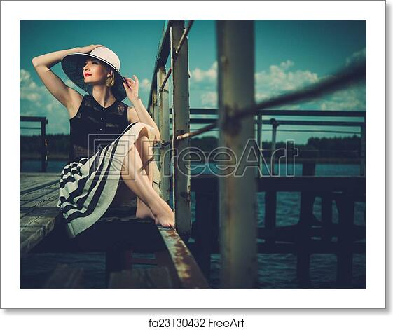 Free Art Print Of Beautiful Woman Wearing Hat And White Scarf Sitting On Old Wooden Pier