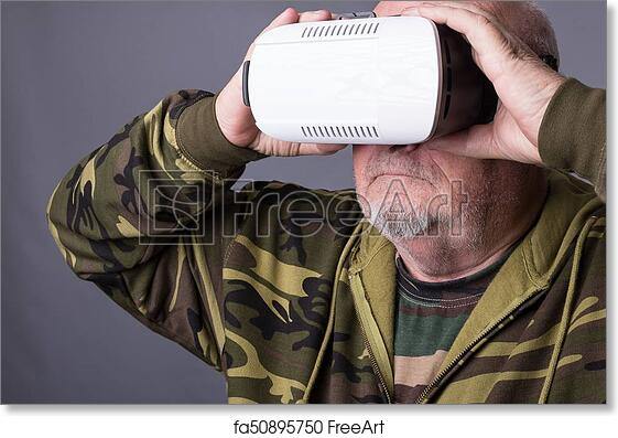 07960b4c317 Free art print of Senior man in wearable technology VR glasses. Confident old  man wearing camouflage clothing in virtual reality headset with Interface  ...