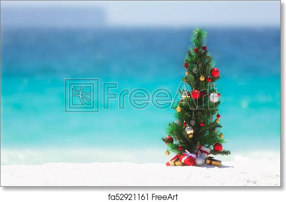 Free art print of Christmas tree on the beach in summer. Christmas tree decorated with colourful baubles and presents underneath it, stands on a beautiful ...